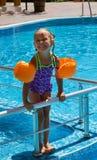 Fille se tenant sur les étapes de la piscine Image libre de droits