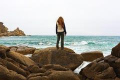 Fille se tenant sur une roche Image stock