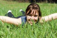 Fille se trouvant sur l'herbe Image stock