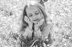 Fille se trouvant sur l'herbe au grassplot, fond vert La fille sur le visage rêveur dépensent des loisirs dehors Concept d'apogée image libre de droits