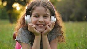 Fille se trouvant sur l'herbe et écoutant la musique sur des écouteurs Le petit enfant caucasien mignon a l'amusement refroidissa banque de vidéos