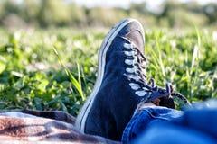 Fille se trouvant sur la couverture sur l'herbe un jour ensoleillé Image stock