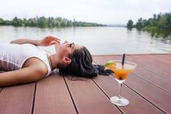 Fille se trouvant sur le dock, se tenant à côté d'un cocktail Images stock