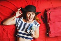 Fille se trouvant sur le lit rouge avec le billet Photo libre de droits
