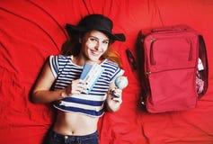 Fille se trouvant sur le lit rouge avec le billet Photos stock