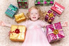 Fille se trouvant sur le plancher entouré par des cadeaux de Noël Image libre de droits