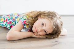 Fille se trouvant sur le plancher et les deams quelque chose Photo stock
