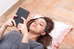 Fille se trouvant sur le plancher, lisant un eBook Photographie stock libre de droits