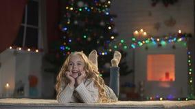 Fille se trouvant sur le plancher près de l'arbre de Noël de scintillement et de la célébration confortable de cheminée banque de vidéos