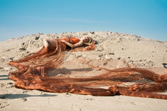 Fille se trouvant sur le sable en tissu orange Photos stock