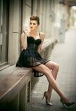 Fille sensuelle avec de longue jambes, robe de noir de short et talons hauts se reposant sur le banc Belle jeune femme utilisant  Photo stock