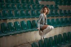 Fille sensuelle avec de longues jambes dans les cours d'un champ Blonde attirante de longues jambes avec les cheveux bouclés déte Photo stock