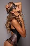 Fille sensuelle dans le corset de lingerie avec de longs cheveux blonds avec le masque de dentelle Photographie stock libre de droits