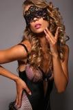 Fille sensuelle dans le corset de lingerie avec de longs cheveux blonds avec le masque de dentelle Photos stock