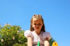 Fille sept ans sur une oscillation sur un fond de ciel bleu Photo stock