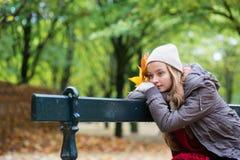 Fille seul s'asseyant sur le banc un jour d'automne Image libre de droits