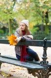Fille seul s'asseyant sur le banc un jour d'automne Image stock