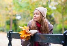 Fille seul s'asseyant sur le banc un jour d'automne Photographie stock
