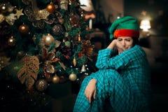 Fille seule de renversement triste pleurant à côté de son arbre de Noël photos libres de droits