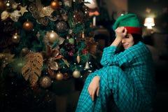 Fille seule de renversement triste pleurant à côté de son arbre de Noël Photographie stock