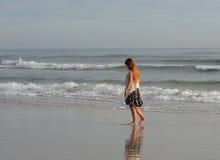 Fille seule marchant sur la plage Image libre de droits