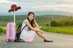 Fille seule s'asseyant sur la route Photo stock