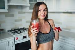 Fille sexuelle de sports tenant une cuvette de fraises et d'un verre de smoothie dans la cuisine photo stock