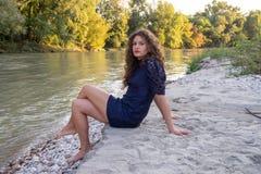 Fille sexy avec de longs cheveux bruns onduleux se reposant sur la banque d'une rivière photos libres de droits