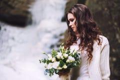 Fille sexy avec un bouquet de mariage des fleurs dans la perspective d'un glacier et des montagnes photographie stock