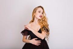 Fille sexy blonde, modèle avec de longs beaux cheveux bouclés posant au studio, sensuel regard, flirtant Noir s'usant photo libre de droits