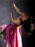 Fille sexy d'élégance dans une jupe rose, balançant sur une oscillation en métal se tenir dessus sur des chaînes Image stock