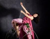 Fille sexy d'élégance dans une jupe rose, balançant sur une oscillation en métal se tenir dessus sur des chaînes Images libres de droits