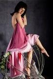 Fille sexy d'élégance dans une jupe rose, balançant sur une oscillation en métal se tenir dessus sur des chaînes Image libre de droits