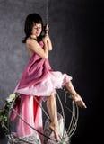 Fille sexy d'élégance dans une jupe rose, balançant sur une oscillation en métal se tenir dessus sur des chaînes Photographie stock