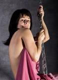 Fille sexy d'élégance dans une jupe rose, balançant sur une oscillation en métal se tenir dessus sur des chaînes Photos libres de droits