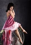Fille sexy d'élégance dans une jupe rose, balançant sur une oscillation en métal se tenir dessus sur des chaînes Images stock