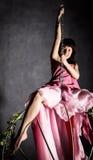 Fille sexy d'élégance dans une jupe rose, balançant sur une oscillation en métal se tenir dessus sur des chaînes Photo libre de droits