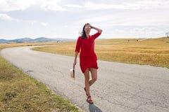 Fille sexy dans la robe rouge se tenant dans un domaine en automne photographie stock