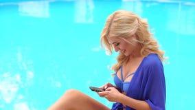 Fille sexy dans le maillot de bain avec le téléphone près de la piscine banque de vidéos