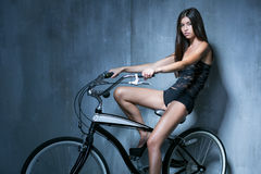 Fille sexy dans un gilet noir et des shorts se reposant sur le vélo sur Photos libres de droits