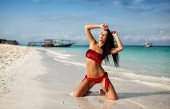 Fille sexy dans un maillot de bain rouge dans une plage de paradis photos stock