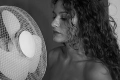 Fille sexy de brune avec les cheveux bouclés avec le ventilateur image libre de droits