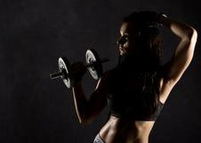 Fille sexy de forme physique avec des haltères sur un fond foncé Athlète faisant des exercices dans le gymnase Photographie stock