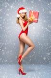 Fille sexy de Santa dans un maillot de bain rouge avec un chapeau de Noël sur la neige Photographie stock