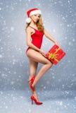 Fille sexy de Santa dans un maillot de bain rouge avec un chapeau de Noël sur la neige Images libres de droits