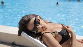 Fille sexy fascinante sur prendre un bain de soleil noir de maillot de bain banque de vidéos