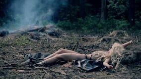 Fille sexy prenant un bain de soleil contre le contexte du feu et des brindilles banque de vidéos