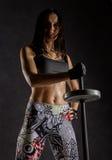 Fille sexy sportive avec le barbell sur un fond foncé Athlète faisant des exercices dans le gymnase Images stock
