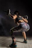 Fille sexy sportive avec le barbell sur un fond foncé Athlète faisant des exercices dans le gymnase Image libre de droits