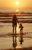 Fille silhouettée et enfant marchant sur la plage au coucher du soleil, San Diego, la Californie Photos libres de droits
